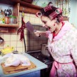 The silly housewife with butcher in hands and carcass of a hen — Stock Photo
