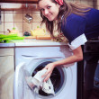 Young housewife with washing machine and towels. — Stock Photo #9509363