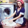Stock Photo: Young housewife with washing machine and towels.