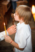 The little boy a kissing cross in church — Stock Photo