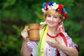Happy Ukrainian woman with a wooden mug — Stock Photo
