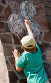 The little boy drawing balloons on a stone wall — Stockfoto