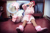 Young housewife with washing machine and towels. — Stock Photo