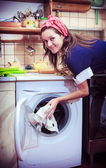 Young housewife with washing machine and towels. — Stockfoto