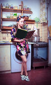 The silly housewife with book and carcass of a hen in hands — Stock Photo