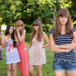 Upset teenage girl with friends gossiping in park - Stok fotoğraf