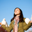 The happy teen releasing a pigeons - Stock Photo