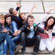 Group of male and female students sitting on street — Stock Photo