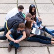 Group of male and female students sitting with a laptop on stree — Stock Photo