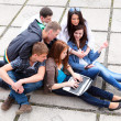Group of male and female students sitting with a laptop on stree — Stock Photo #9523053