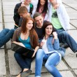 Group of male and female students sitting with a laptop on stree — Stock Photo #9523057