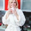 Beautiful young caucasian woman in the kitchen with cup tea — Stock Photo