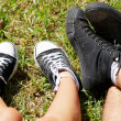 Feet of teenagers and gym shoes on a green grass of a lawn in p — Stock Photo #9523528