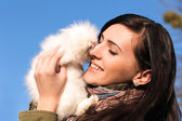 Young girl holding a white little rabbit — Stock Photo