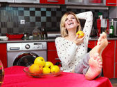 Pretty smiling young woman sit in the kitchen with fruit — Stock Photo