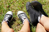Feet of teenagers and gym shoes on a green grass of a lawn in p — Stock Photo