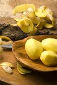 Batatas cruas e as cascas de batata — Fotografia Stock
