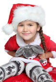 Portrait of happy little girl with toy in santa claus clothes — Stock Photo