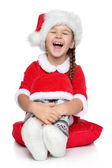 Happy little girl in Santa hat laughs on a white background — Stock Photo