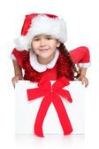 Happy little girl in Santa hat looks out of gift box — Stock Photo