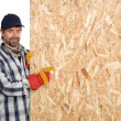 Carpenter points a sheet of plywood - Stock Photo