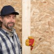 Carpenter holds a plank - Stock Photo