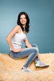 Girl in jeans sitting on the couch — Stock Photo