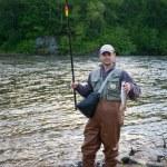 Happy fisherman holds captive salmon. — Stock Photo