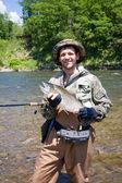 Rybak trzyma złowionych łososia wiśnia — Zdjęcie stockowe