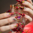 Manicure of beautiful hands with a glass — Stock Photo
