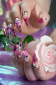 Beautiful manicure of hands with a rose — Stock Photo