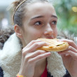 Teenage girl eating sandwich — Stock Photo
