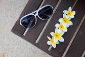 Flores tropicais e óculos de sol no banco — Fotografia Stock