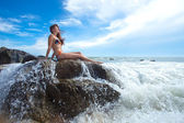 Woman on the rock in ocean — Stock Photo
