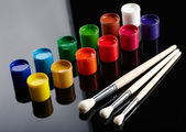 Paint buckets with paintbrushes over dark background — Stock Photo