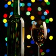 Wine bottle and glass over holiday background - Stock Photo