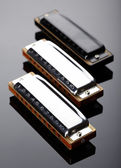 Tree harmonicas on dark background — Stock Photo