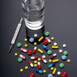 Pills, thermometer and glass of water over dark background - Stock Photo