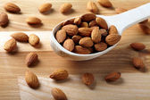 Almonds on wooden background — Stock Photo