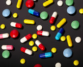 Colorful pills over dark background — Stock Photo