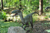 Life size statue of a velociraptors in forest scenery — Stock Photo