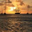 Caribbean sunset and silhouett of the ship and sailboats — Stock Photo
