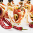 Canape with prosciutto and olives — Stock Photo