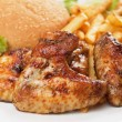Grilled chicken wings with french fries - Stock Photo
