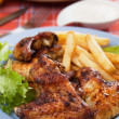 Stock Photo: Grilled chicken wings with french fries
