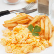 Scrambled eggs and french fries - Stock Photo