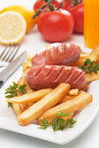 Salsichas grelhadas com batatas fritas — Fotografia Stock