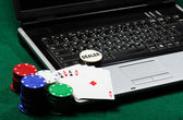 Gambling chips and poker cards on a laptop — Stok fotoğraf