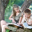 Young guy and the girl with textbooks on the bank of lake — Stock Photo #10053673