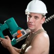 The builder in a protective helmet holds the professional puncher-hammer with a drill of the big diameter - Foto de Stock